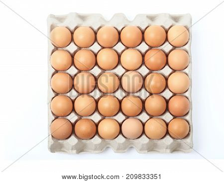 Top view of farm fresh chicken eggs in tray isolated over white background, clipping path.