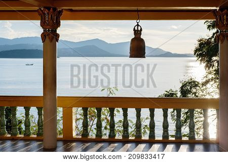 Terrace with columns, Buddhist bell, view of the sea and mountains in the distance. The rays of the pre-dawn sun are reflected in the water. Thailand.