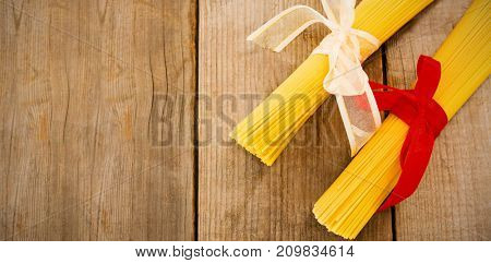 Overhead view of raw spaghetti tied with ribbons on wooden table