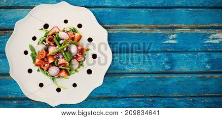 Overhead view of fresh salad in white plate served on blue wooden table