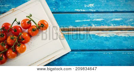 Overhead view of cherry tomatoes on white cutting board