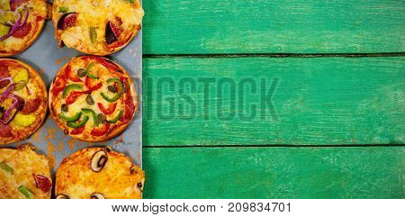 Overhead view of pizzas arranged on green wooden table