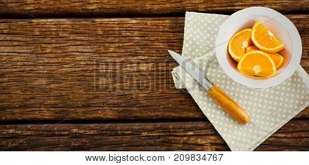 Overhead view of orange slices in bowl with knife and napkin on wooden table