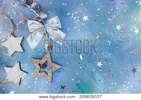 Wooden Christmas Star And Silver Bow On Blue Background
