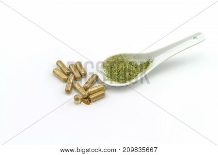 Herbal capsule and powder in white ceramic spoon on white background.