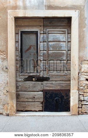 Rustic wooden doors whose glass cuttings have been partially replaced with metal and wood boards, locked with large padlock in stone frame and wall