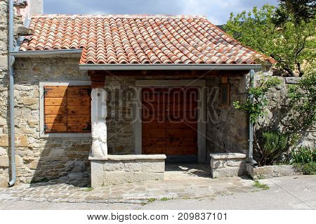 Traditional Mediterranean stone house with new roof tiles, wooden windows blinds and drain pipe