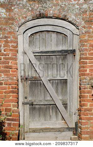 Old unpainted wooden door in brick wall