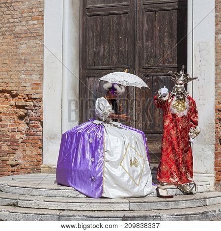 VENICE ITALY - SEPTEMBER 22 2017: Beautiful dressed women and man in traditional Venetian costume. The tradition of Venetian masks began in Venice in the 11th century