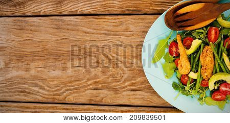 Overhead view of fresh salad in blue plate on brown wooden table