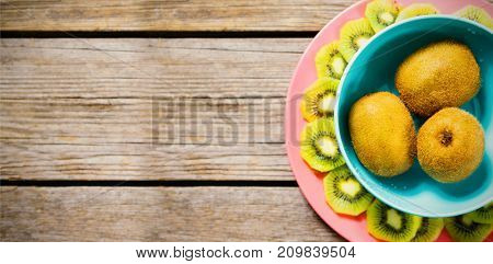 Overhead view of kiwi fruits arranged in bown and plate on wooden table