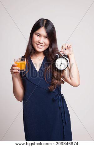 Asian Woman With A Clock Drink Orange Juice.