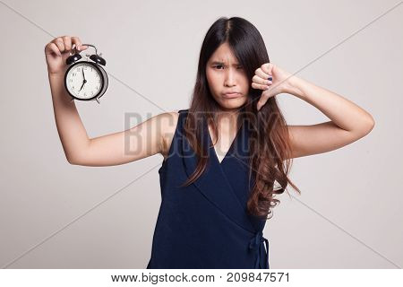 Young Asian Woman Thumbs Down With A Clock.
