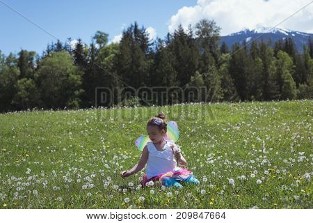Girl plucking flower in park