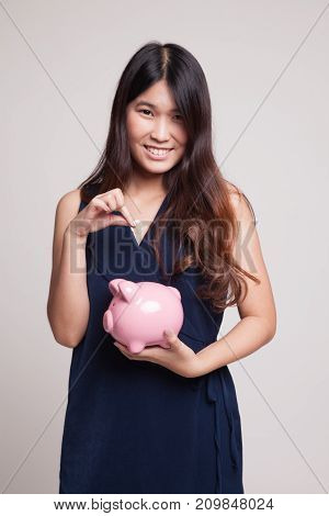 Asian Woman With Coin And Pig Coin Bank.
