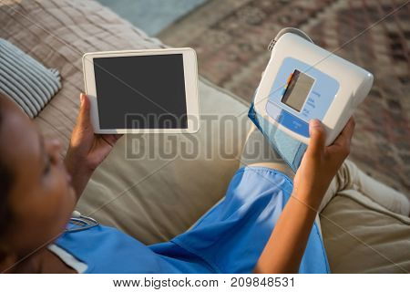 Doctor holding blood pressure monitor and digital tablet in hospital