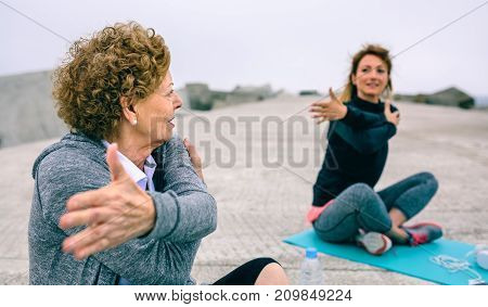 Senior woman stretching with female coach by sea pier