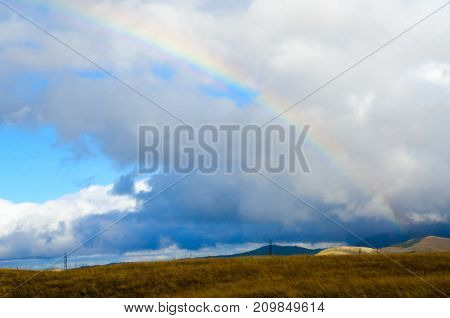Rainbow after rain in vicinity of Zabljak mountains in background Montenegro