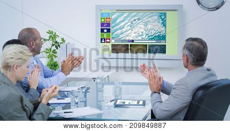 Business team applauding and looking at white screen against digitally generated image of various video and icons displayed