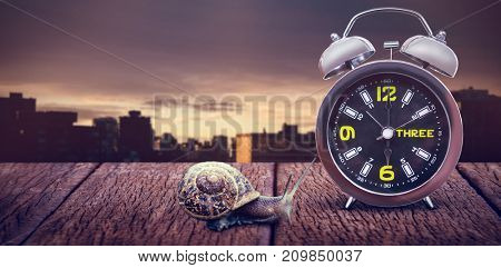 Close up of alarm clock against city against cloudy sky during sunset