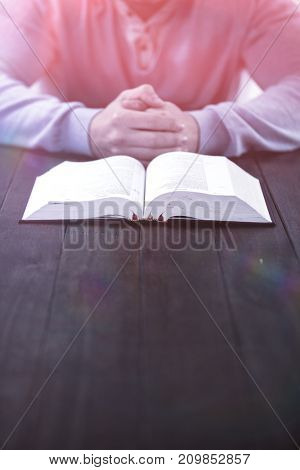 Mid section of man with bible praying at wooden table