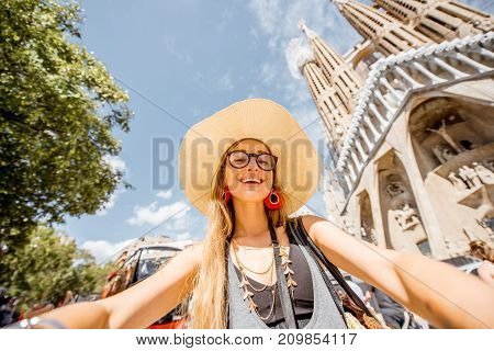 BARCELONA, SPAIN - August 16, 2017: Young woman tourist photographing in front of the famous Sagrada Familia unfinished Roman Catholic church in Barcelona, designed by Catalan architect Antoni Gaudi