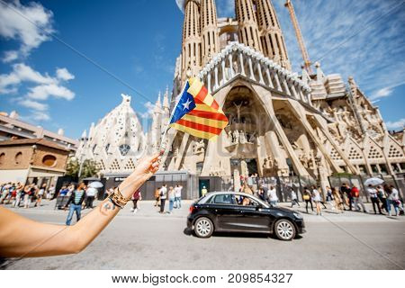 BARCELONA, SPAIN - August 16, 2017: Holding catalan flag in front of the famous Sagrada Familia Roman Catholic church in Barcelona, designed by architect Antoni Gaudi