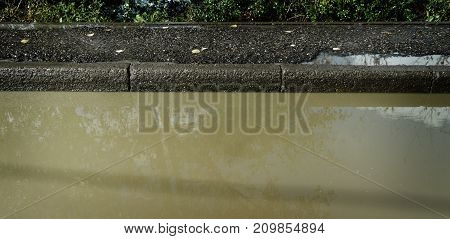 Puddle of dirty water. Street after rain. Puddle. Nature gunge. Grunge puddle. Grey colors nature. Grey grunge nature background. Autumn puddle.