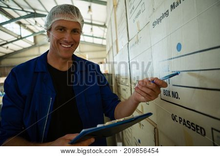Portrait of worker maintaining record on clipboard in olives factory