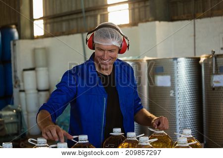 Smiling worker checking a can of olives oil in factory