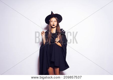 a young sexy gothic girl in the form of a witch in halloween, in a big black hat, adorned with yellow leaves, holds a magic wand in her hand