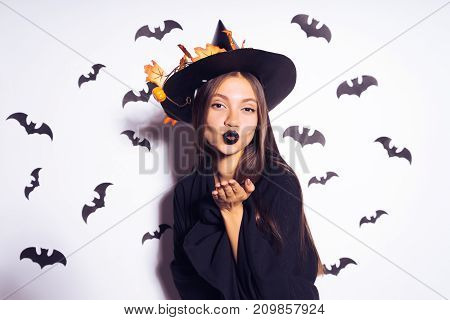 a young sexy gothic girl in the shape of a witch in halloween, in a big black hat, adorned with yellow leaves sends an air kiss