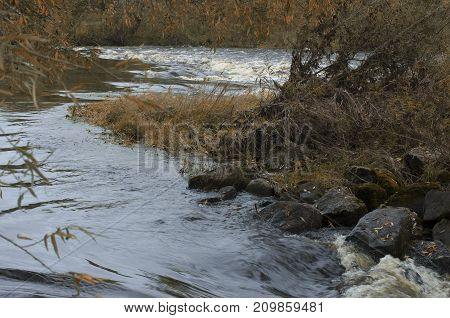 Chaotic autumn landscape with the river and the overgrown and littered with river ledge