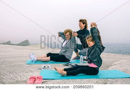 Three female generations exercising by sea pier