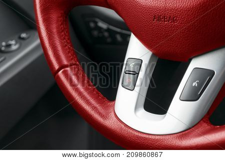 Hands free and media control buttons on the red steering wheel in black leather modern car interior
