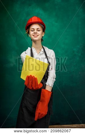 smiling girl in a large apron and wearing orange gloves shows a yellow rag in the camera