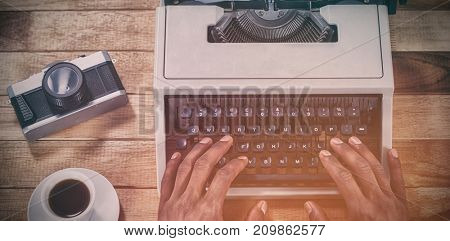 Cropped hands of businessman using typewriter by vintage camera and coffee on table