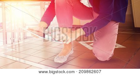 Low section of businesswoman kneeling while using digital tablet against foyer area with elevator