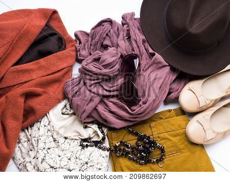 Flat lay with lady's clothes, hat, sun glasses, necklace. Autumn colours accessories and shoes on white background