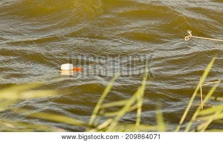 Fishing rod on the river bank in the nature