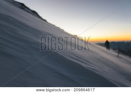 The blurred mountaineer professionally equipped at dawn of the sun walks on the slope in the early morning and the snow drifts over the snow above the snow. The concept of travel and conquest of steep peaks