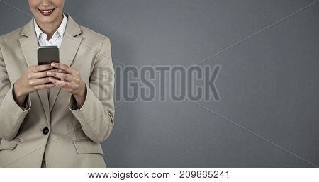 Beautiful businesswoman using mobile phone against grey background