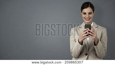 Smiling businesswoman using mobile phone against grey background