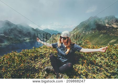 Woman meditating in mountains yoga lotus pose Travel Lifestyle adventure concept harmony with nature summer vacations outdoor