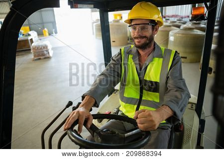Smiling worker driving a forklift car in factory