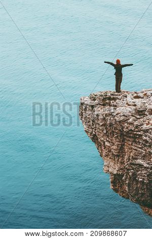 Happy traveler standing on cliff above sea hands raised Travel Lifestyle success motivation concept adventure active vacations outdoor
