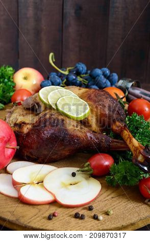 Baked goose legs served with apples vegetables grapes greens on a round oak tray on a dark wooden table. Vertical view