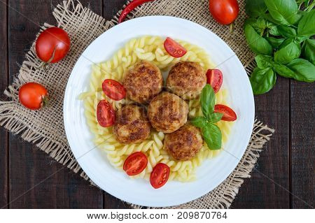 Pasta futsilli with meat balls cherry tomatoes basil on a white plate on a dark wooden background. Top view.