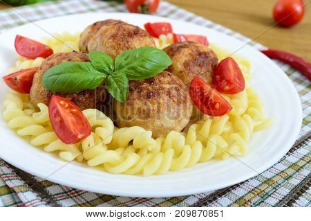 Chicken meat balls pasta fusilli tomatoes basil on a white plate on a wooden background
