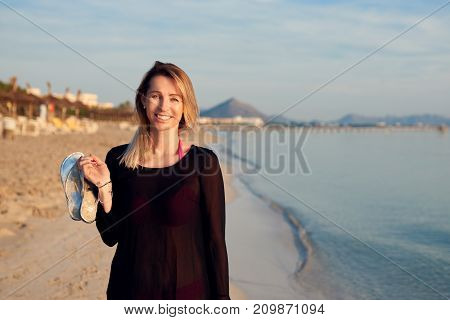 Blond Smiling Woman Walking Along Tropical Beach